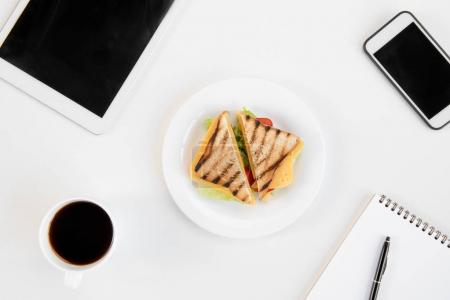 Top view of tasty sandwiches on plate, cup of coffee, notebook with pen, smartphone and digital tablet at workplace