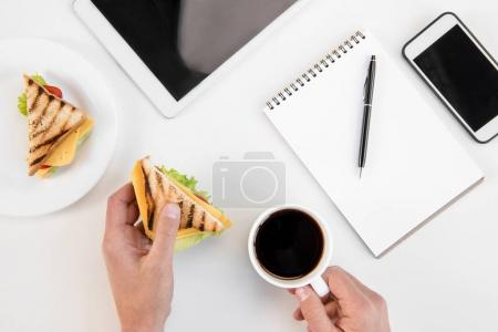 Top view of person eating sandwiches and drinking coffee at workplace with electronics