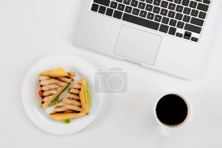 Top view of tasty sandwiches on plate, cup of coffee and laptop at workplace