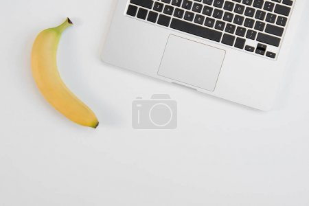 Top view of laptop and fresh ripe banana isolated on grey background