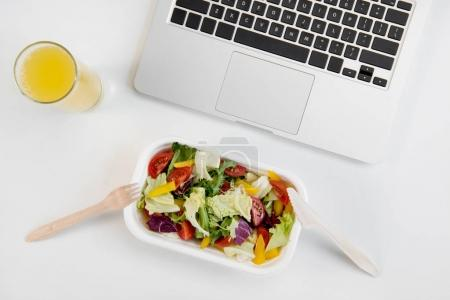 Top view of laptop, orange juice in glass and fresh salad in lunch box with plastic utensils at workplace