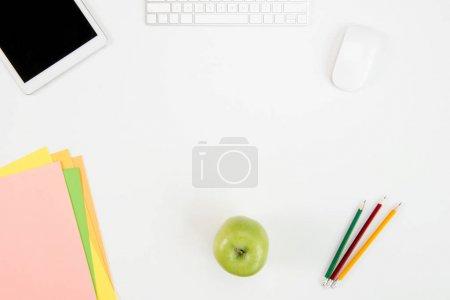 Photo pour Vue de dessus du clavier, souris d'ordinateur, tablette numérique avec écran blanc, pomme verte et Bureau fournit au milieu de travail - image libre de droit