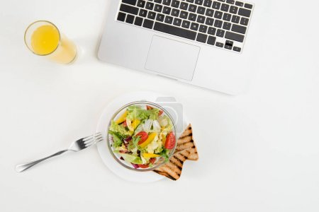 Photo for Top view of laptop, orange juice in glass and fresh healthy salad with toasts at workplace - Royalty Free Image
