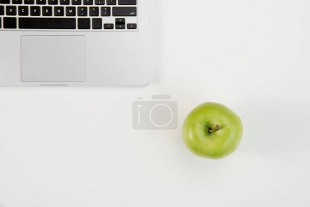 Top view of open laptop and fresh green apple isolated on grey background