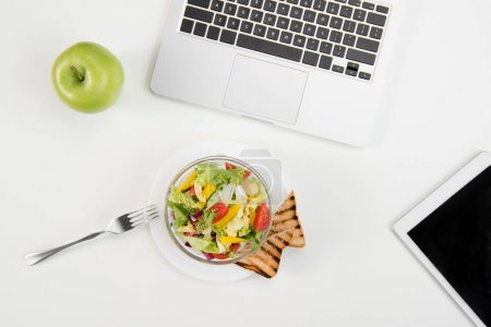 Top view of laptop and digital tablet with blank screen, fresh green apple and fresh salad with toasts at workplace