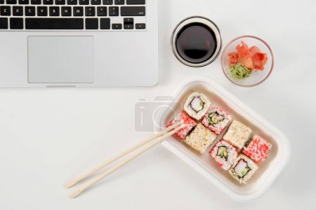 Top view of open laptop and sushi rolls with wasabi and soy sauce at workplace