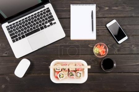 Photo for Top view of laptop with computer mouse, blank notebook with pen, smartphone and sushi set on wooden table - Royalty Free Image