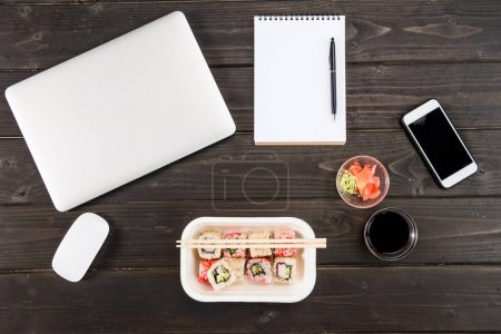 Top view of laptop with computer mouse, blank notebook with pen, smartphone and sushi set on wooden table