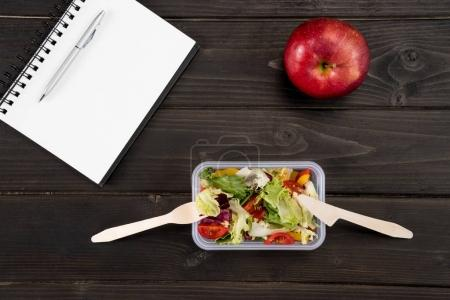 Top view of natural salad with red apple and notebook on wooden surface