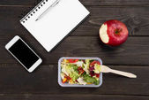 Top view of organic salad with apple, notebook and smartphone on wooden table