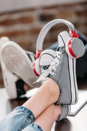 Close-up view of woman's feet in stylish shoes with headphones on wooden table