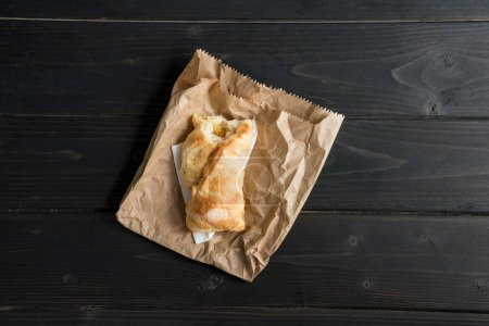 Top view of bitten pastry bun on paper bag on wooden table