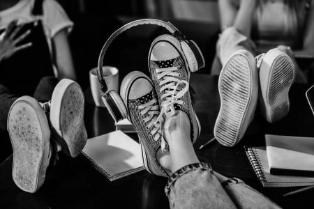Photo for Close-up view of woman's feet in stylish shoes with headphones on wooden table, black and white photo - Royalty Free Image