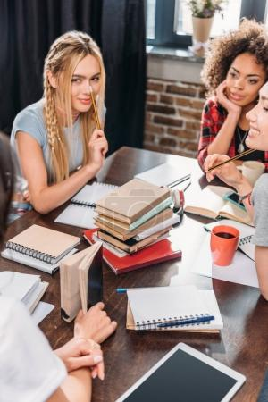Photo for Beautiful young women sitting together at table and studying with books and notebooks - Royalty Free Image