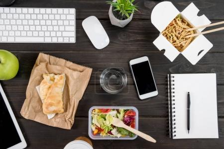 top view of digital devices with food with glass of water mock-up on tabletop