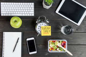 Top view of digital devices with apple and salad with alarm clock mock-up on tabletop