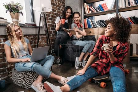 Smiling young women sitting together with laptop and coffee cups, studying and talking indoors