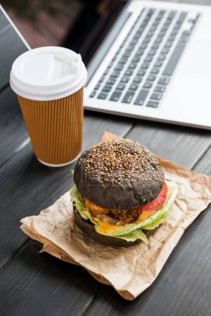 Photo for Close up of burger with coffee to go and laptop on wooden tabletop - Royalty Free Image
