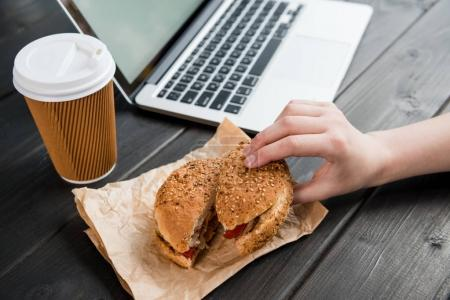 close up of hand holding burger with coffee to go and laptop on wooden tabletop