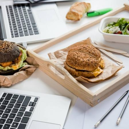 Close up of tasty burgers with fresh salad and bread loaf with laptops on tabletop