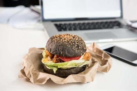 close up of tasty burger with black bun on tabletop at workplace