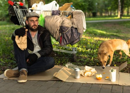 Homeless man with stray dog sitting in city park and holding bottle of alchohol.