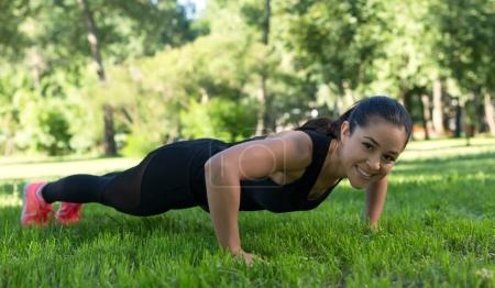 Young brunette woman doing push up exercise on the grass outdoors.