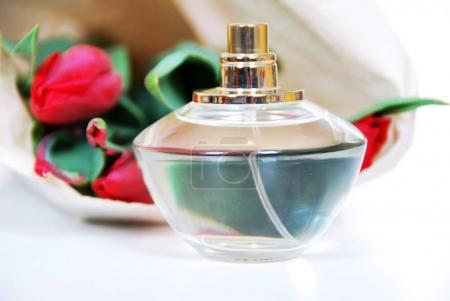 Blütenduft in einer Glasflasche und rote Tulpen