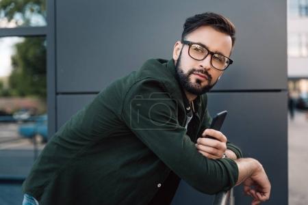man in eyeglasses holding smartphone