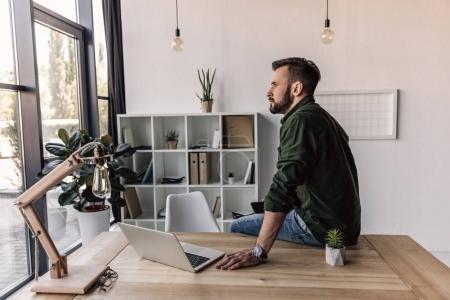 Photo pour Homme barbu assis sur table avec ordinateur portable au bureau moderne - image libre de droit