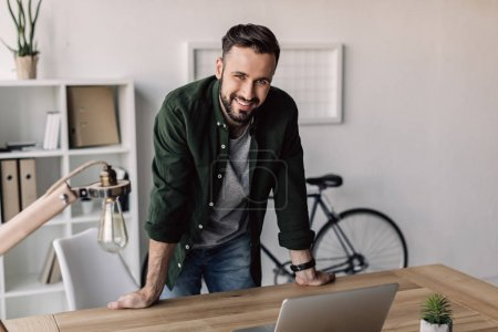 Photo for Smiling bearded businessman leaning on table in modern office - Royalty Free Image