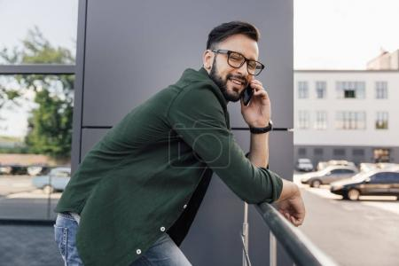 Photo for Smiling bearded young man in eyeglasses using smartphone - Royalty Free Image