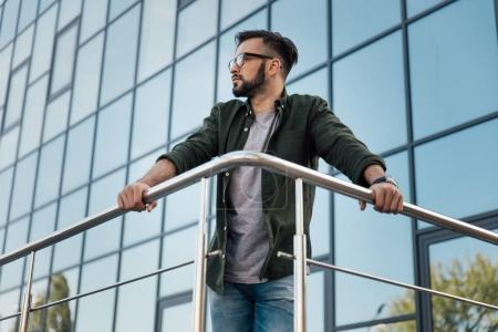 Photo for Young bearded man in eyeglasses leaning on railing at office building - Royalty Free Image