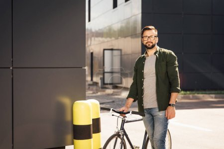 man standing with bicycle