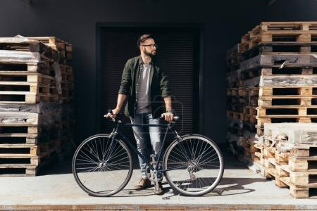 Photo for Stylish young man standing with bicycle and looking away - Royalty Free Image