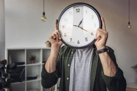 Photo for Young man holding wall clock while standing in office - Royalty Free Image