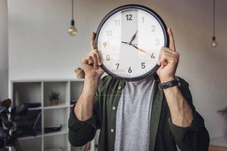 Photo pour Jeune homme tenant horloge murale en se tenant debout dans le Bureau - image libre de droit