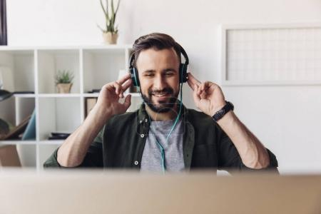 Photo for Smiling bearded man listening music in headphones while sitting in office - Royalty Free Image