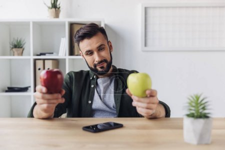 Photo for Smiling bearded businessman choosing between green and red apples while sitting at office table - Royalty Free Image