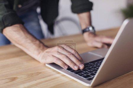 Photo pour Plan recadré de l'homme à l'aide d'un ordinateur portable à la table en bois - image libre de droit