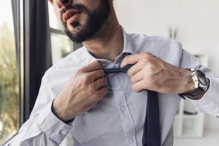 Photo pour Plan recadré de jeune homme d'affaires barbu en chemise ajustant la cravate - image libre de droit