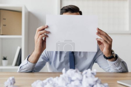 Photo for Obscured view of businessman covering face with blank paper in hands - Royalty Free Image