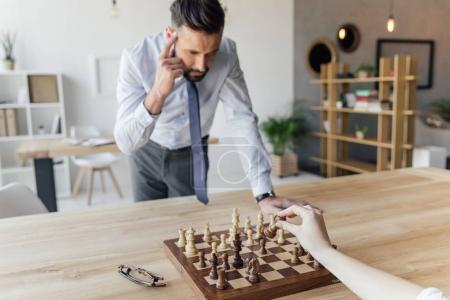 Photo for Focused businessman playing chess with colleague in office - Royalty Free Image