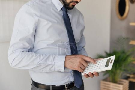 Photo for Partial view of businessman making counts on calculator in hands - Royalty Free Image