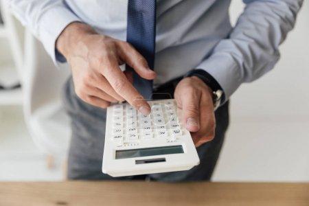 Photo pour Vue rapprochée de l'homme d'affaires compte sur la calculatrice dans les mains - image libre de droit