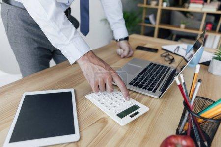 Photo pour Plan recadré de l'homme d'affaires en utilisant une calculatrice tout en travaillant sur le lieu de travail dans le bureau - image libre de droit