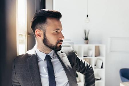 Photo pour Portrait de bel homme d'affaires en tenues en regardant loin bureau moderne - image libre de droit