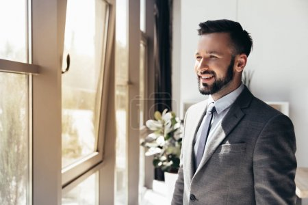 Photo for Portrait of smiling businessman in formal wear looking away at modern office - Royalty Free Image