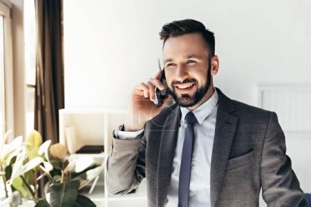 smiling businessman talking on smartphone at office