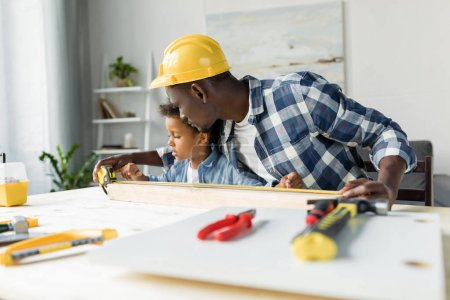 african-american father and son doing renovation